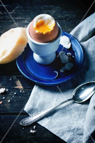 Breakfast with soft-boiled egg, served with bread over old wooden table