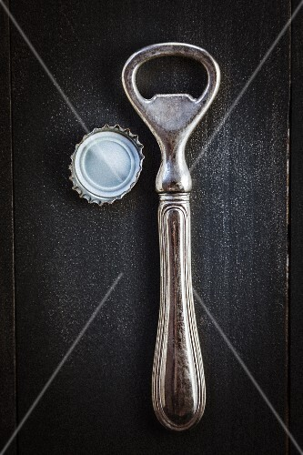 An antique bottle opener and bottle top