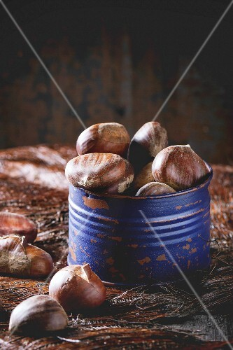 Purple Tin jar with raw edible chestnuts over wooden table