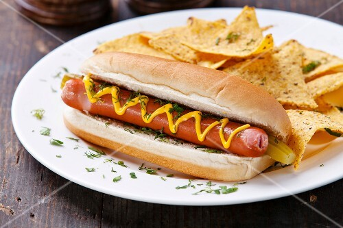 Hot dog with mustard and potato chips on wooden background