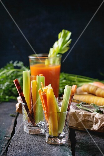 Sliced colorful raw carrots and celery as vegetarian snack and glass cup of fresh orange and carrot juice