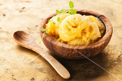 Mango ice cream sorbet in olive wood bowl
