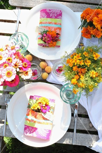 Summery table set for two with colourful posies on rustic garden table