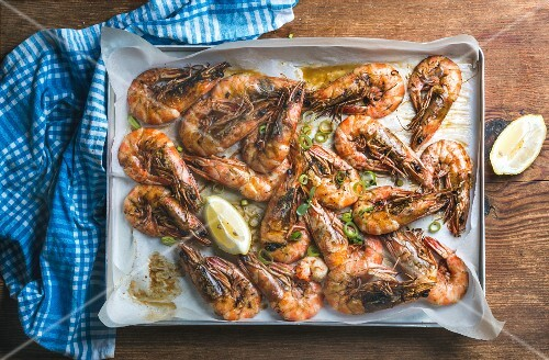Grilled tiger prawns with leek, herbs and lemon in silver tray over wooden background