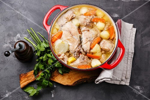 Stewed rabbit with potatoes and carrot in cast iron pot on concrete background