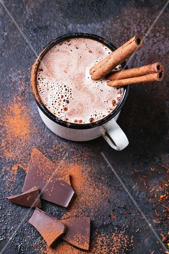 Vintage mug of hot chocolate with cinnamon sticks over dark background