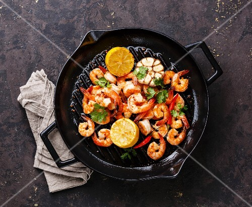 Prawns roasted on frying grill pan with lemon and garlic on dark background