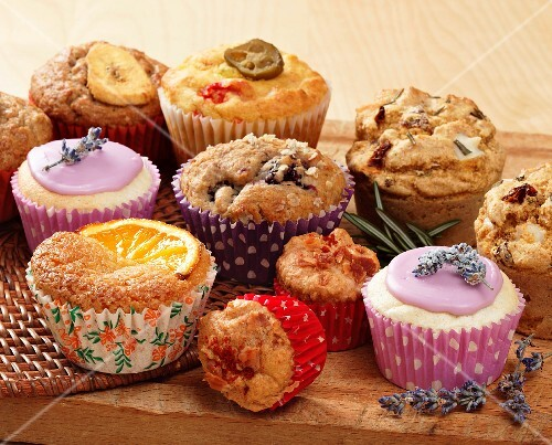 A selection of muffins and cupcakes on a wooden board