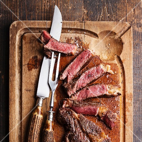 Medium rare Beef steak Ribeye with knife and fork for meat on cutting board on dark wooden background