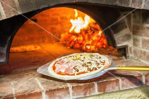 Pizza capricciosa in front of a wood oven