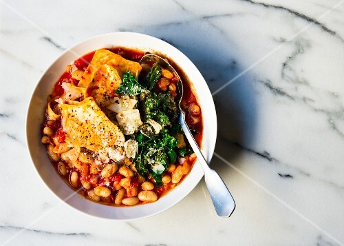 Cannellini beans and pasta in a tomato soup topped with kale and cheese