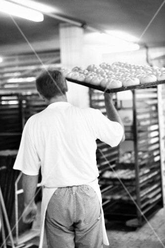 A baker carrying a baking tray of baked bread rolls