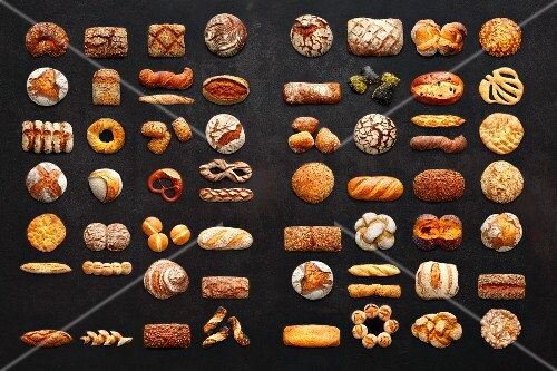 Various types of bread on a dark background (seen from above)