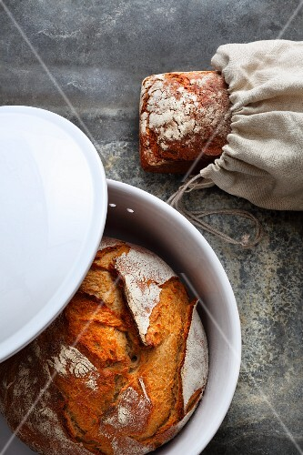 Bread being stored correctly in an earthenware dish and a cloth bag