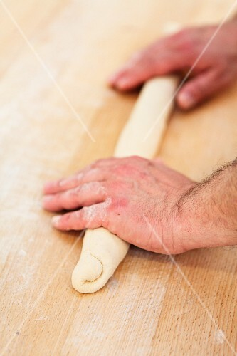 Dough being rolled into a baguette shape