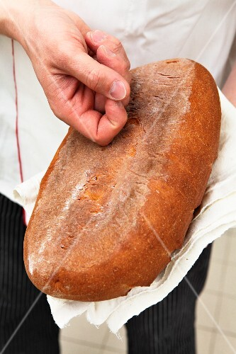 A baker tapping the bottom of a loaf of bread