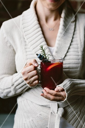 A woman with a glass of blueberry hot toddy in her hand