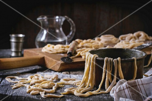 Fresh homemade pici pasta on wood chopping board with flour, copper bowl, rolling-pin and glass jug of water