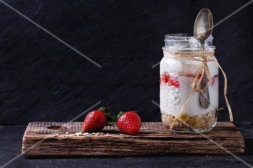 Muesli, strawberries and yogurt in glass mason jar with spoon. Yoghurt served on wooden chopping board