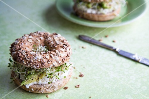 Whole wheat bagels with avocado, sprouts and cream cheese