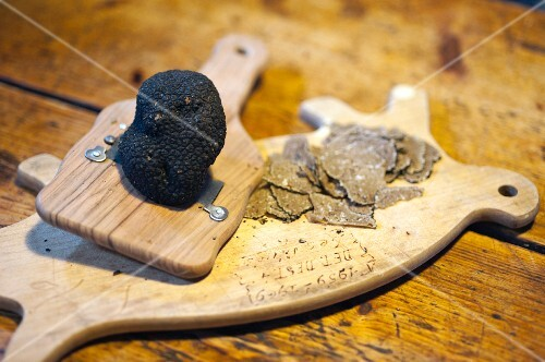 A piece of burgundy truffle on a wooden board with a planer