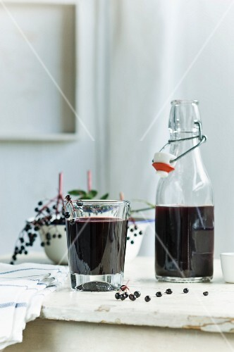 Homemade elderberry juice in a bottle and a glass