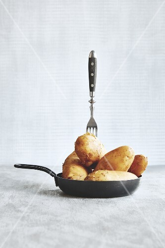 A fork in raw, unpeeled potatoes in a frying pan