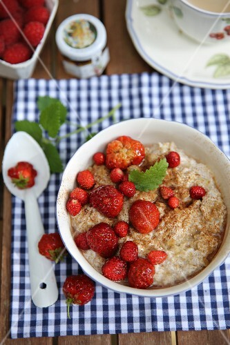 Summer breakfast porridge with strawberries on a garden table