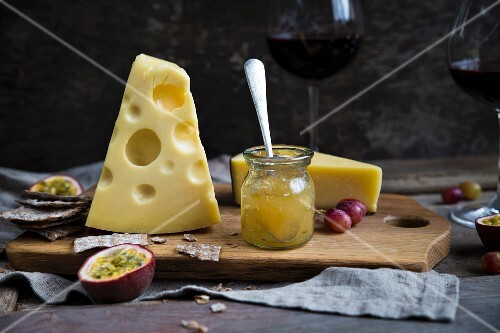 Cheese board with jam, fruit and wine