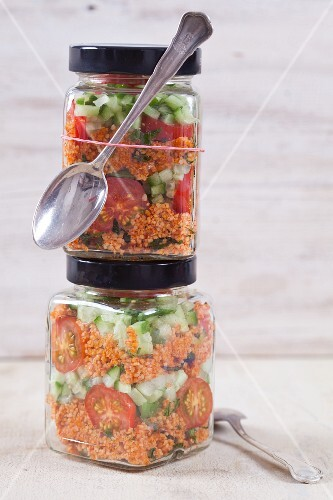 Bulgur wheat salad with pomegranate syrup, onions, cucumber, tomatoes, parsley and mint in a glass jar