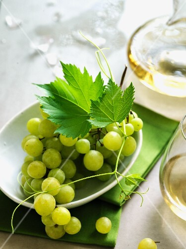 Green grapes with a glass of white wine and a carafe