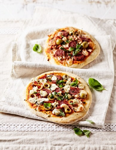 Two rustic pizzas with chorizo, green olives and basil leaves