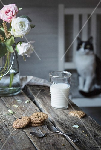 A glass of milk and biscuits on wooden table