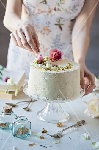 Woman is decorating a chiffon cake on marble table