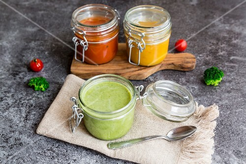 Various colourful soups in glass jars (broccoli soup, tomato soup, pumpkin soup))