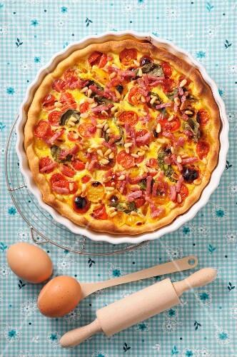 Quiche with cherry tomatoes, spinach, bacon and pine nuts