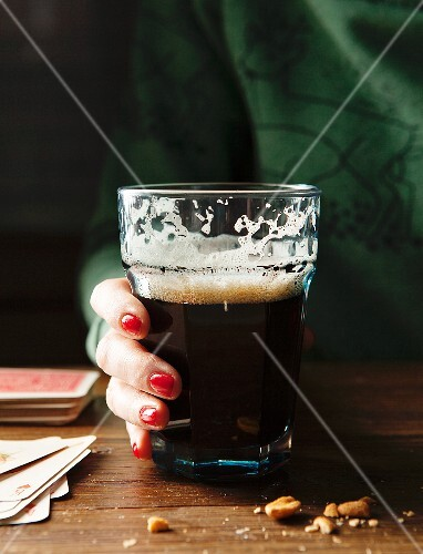 Glass of drunk Guinness with a ladies hand with red nails and a green sweater holding glass at a wooden table surrounded by nuts and playing cards