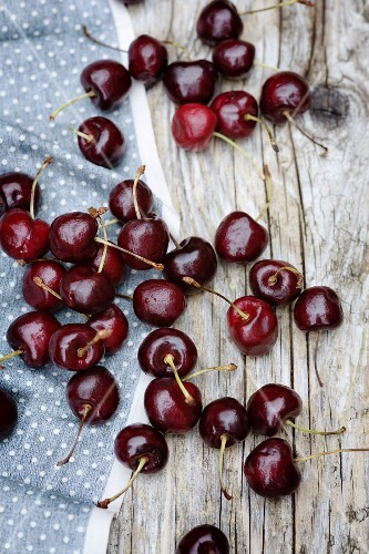 Cherries scattered on a wooden table