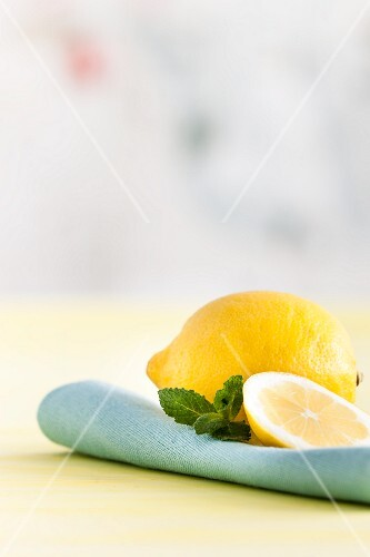 A whole lemon, a slice of lemon, and mint leaves