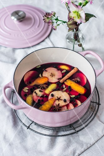 Advent punch with apple slices and spices in a cooking pot