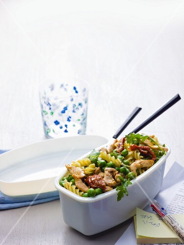 A pasta salad with fusilli, chicken, peas and dried tomatoes