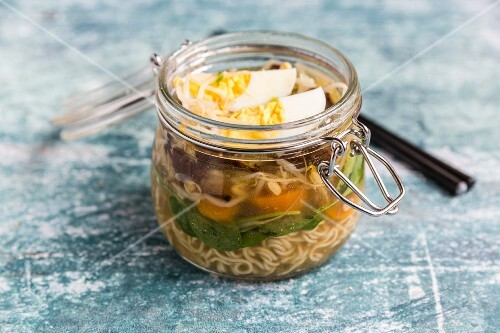 Ramen soup with spinach, bamboo shoots, carrots, egg and mushrooms in a glass jar