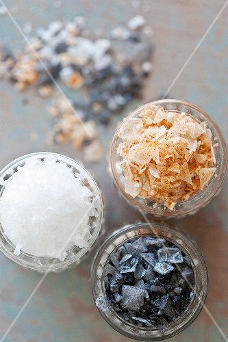 Black salt, paprika salt and sea salt flakes in glasses