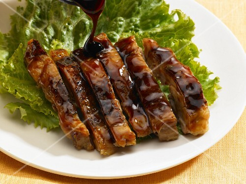 Asian ribs with sauce on a bed of lettuce