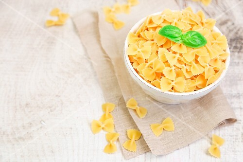 Farfalle pasta in a bowl on wood table