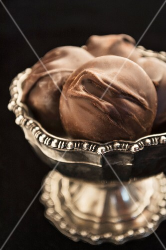 Chocolate confectionery with macadamia nuts in a silver bowl (close up)