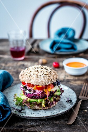 A veggie burger with wholegrain bread, lentils, avocado, sheep's cheese and tomatoes