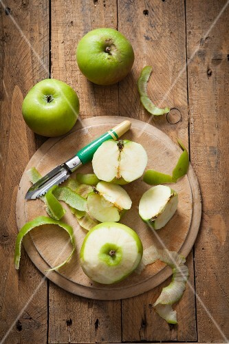 Green Bramley apples, whole and peeled, with an apple peeler