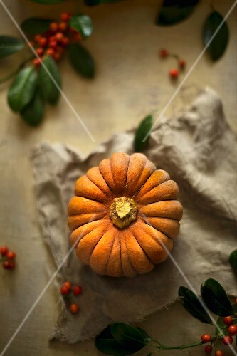 A whole Muscat pumpkin with berries on a linen cloth (top view)