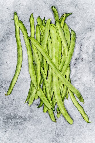 Fresh green beans on a grey background (top view)